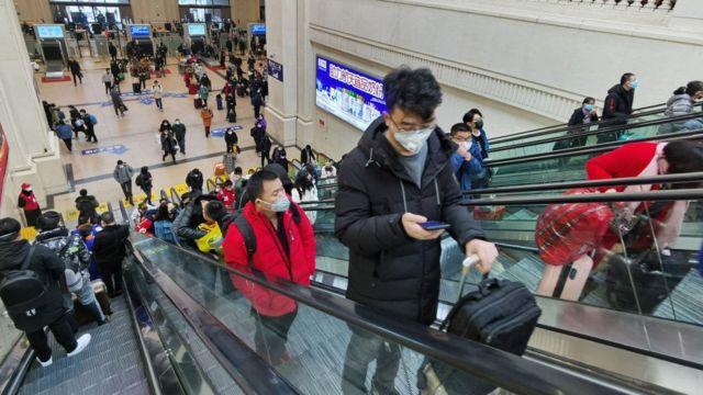 People wearing face masks ride escalators inside Hankou Railway Station on January 22, 2020 in Wuhan