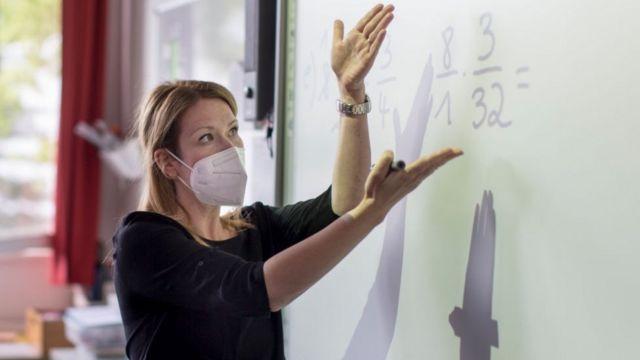 Profesora con mascarilla en un aula