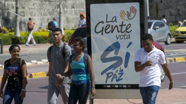 Colombianos pasan junto a un cartel del Sí al plebiscito nacional