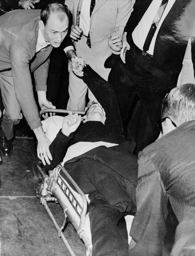 Oswald é levado às pressas para uma ambulância após ser baleado por Jack Ruby