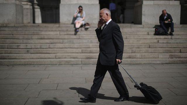 Работник Сити с чемоданом и мобильным