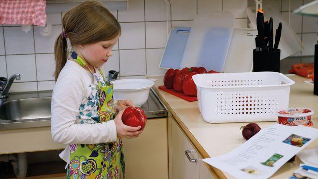 Niña en clase de cocina con un morrón en la mano en Norssi, la escuela normal de la Universidad de Jyvaskyla