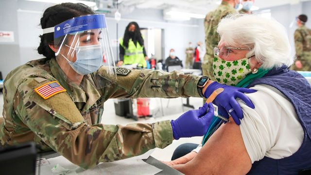 A US Army medic administers a coronavirus vaccine to an elderly woman at a vaccination centre in Illinois - 3 February 2021