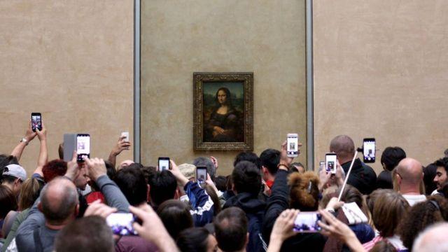 La Mona Lisa de Leonardo da Vinci siendo fotografiada con celulares en el Museo Louvre.
