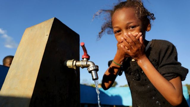 Uma criança toma água em uma torneira em uma vila em Madagascar