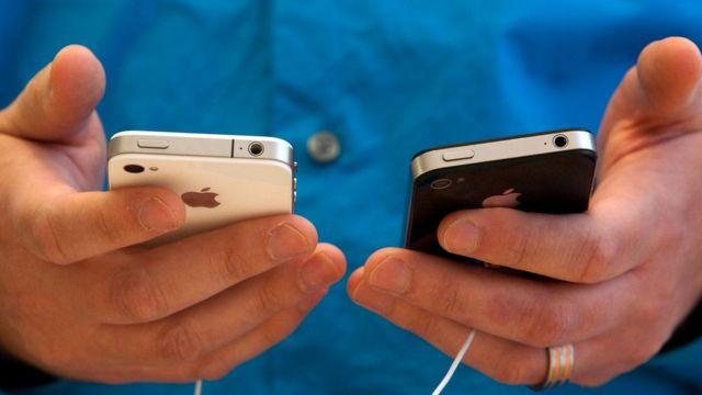 iki iPhone tutan adam
