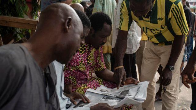 Nigerian men examine a newspaper after the postponement