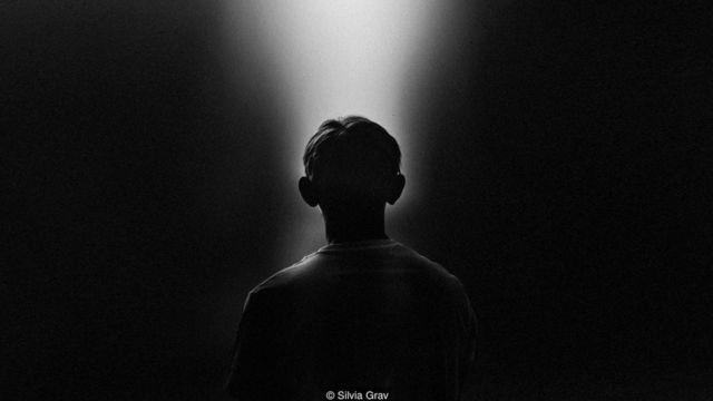 Foto en blanco y negro de una persona mirando una luz. Foto: Silvia Grav.