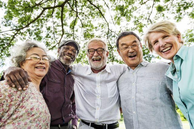 five elderly people hug and smile