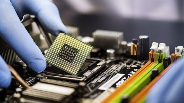 Mão de luva azul segura um semicondutor