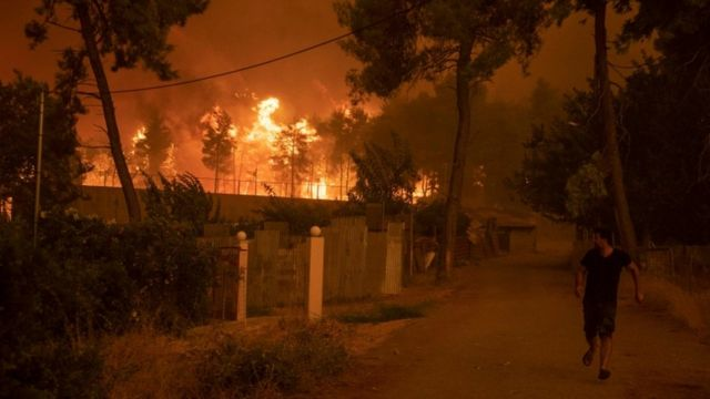 A man walks away from a fire on the Greek island of Evia.