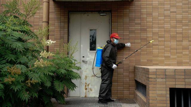 Un voluntario desinfectando un apartamento en Pekín.