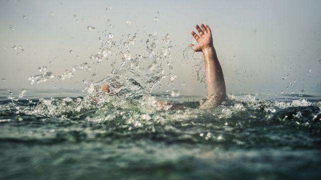 Pessoa com o braço levantado na água