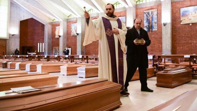 Интерьер церкви, священник освещает гробы