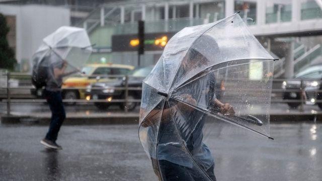 Люди под зонтами в районе токийского вокзала Синдзюку (12 октября 2019 года)