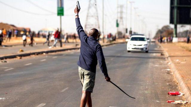 Elinde silah tutan bir adam havaya ateş ediyor