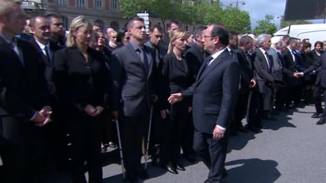 President Hollande tries to shake the hand of a policeman at a ceremony for the murdered police couple on 17 June 2016