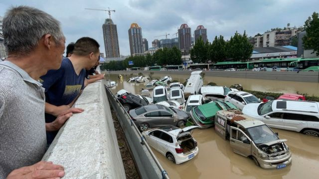 People look out at cars sitting in floodwaters after heavy rains hit the city of Zhengzhou