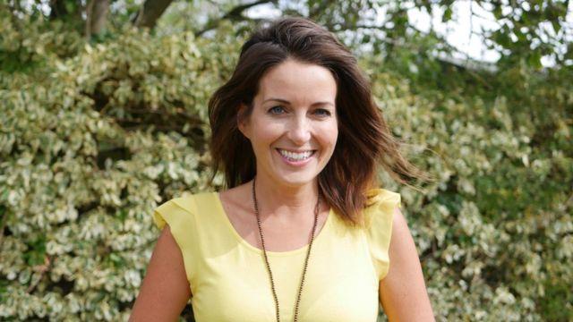 Gemma McGough posa sorrindo em jardim