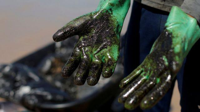 Pessoa mostra luvas sujas de óleo