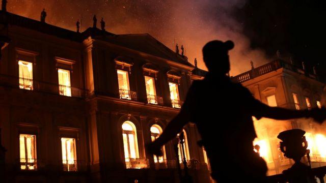 Policajac ispred zgrade u plamenu.