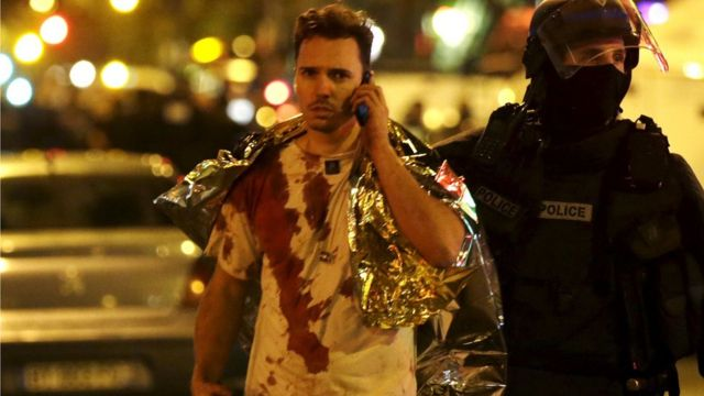 A French policeman assists a blood-covered victim near the Bataclan concert hall following attacks in Paris, France, November 14, 2015.