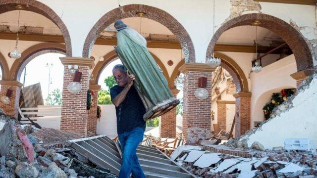 Un hombre cargando la estatua de San Judas entre los escombros de la parroquia de la Inmaculada Concepción