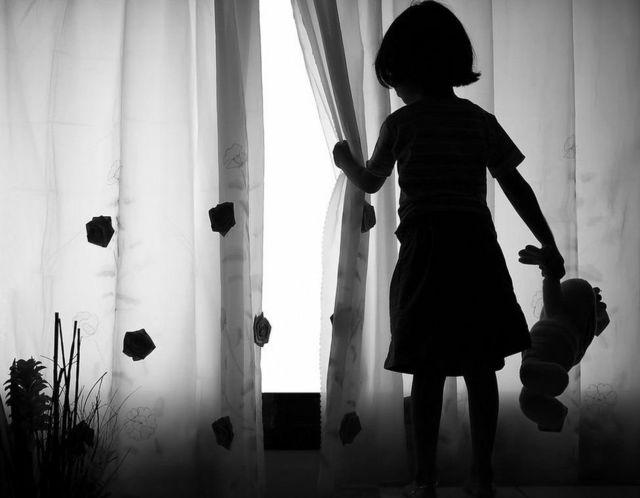 small girl wey dey look outside from window