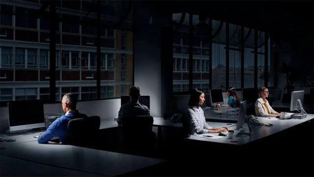 Personas trabajando en una oficina oscura