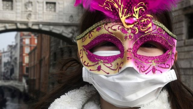 A person in a decorative mask and a face mask at the Venice Carnaval