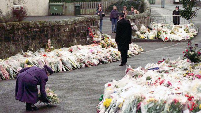 La Reina poniendo flores en la Escuela Primaria de Dunblane