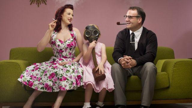 Porodica na krevetu. Majka sa cigaretom, otac sa lulom, dete sa gas maskom