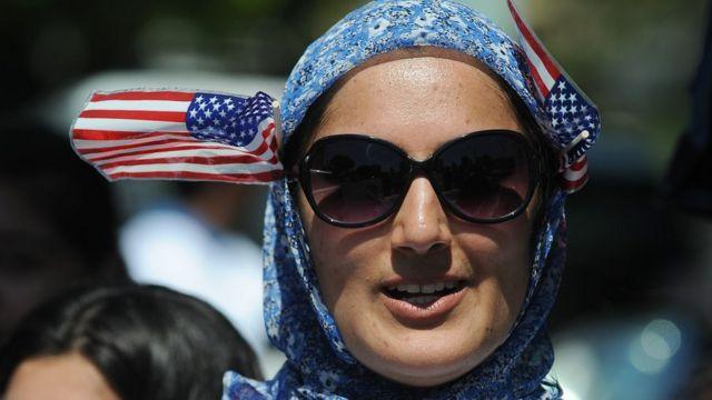 Una mujer con velo y banderitas de EEUU