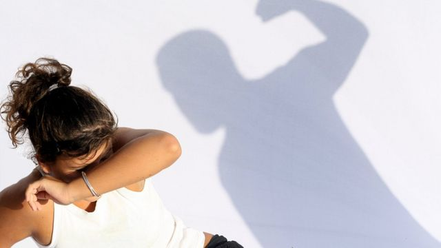 A woman threatened by the shadow of a man with a raised fist