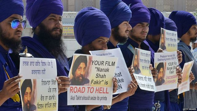 Activists of Sikh Nihangs - religious Sikh warriors - from the Jatha Neeliyan Faujan organization hold placards as they protest against the film 'Nanak Shah Fakir' outside the Golden temple in Amritsar on April 9, 2015.