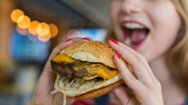 Mulher come hambúrguer