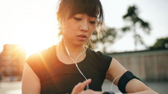 મોબાઇલના ઇઅરફોન પર કંઈક સાંભળતી એક યુવતી