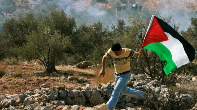 فلسطيني يحمل علم بلاده