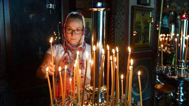 Прихожанка російської православної церкви Святої Богородиці в Сіднеї, Австралія, запалює свічку на Святвечір