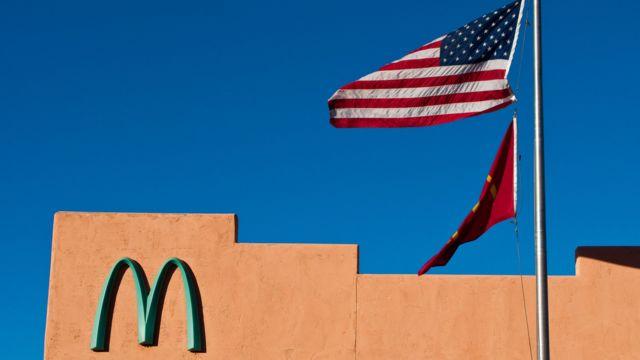 El logotipo de la compañía junto a una bandera de EE.UU.