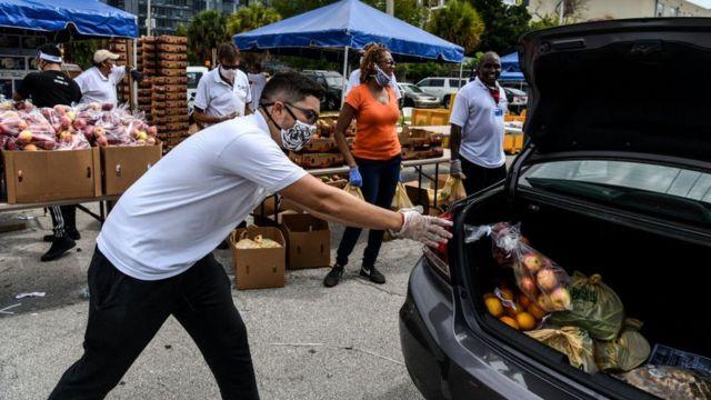 Homem retira saca de cebola do porta-malas de um carro para abastecer centro de distribuição de alimentos