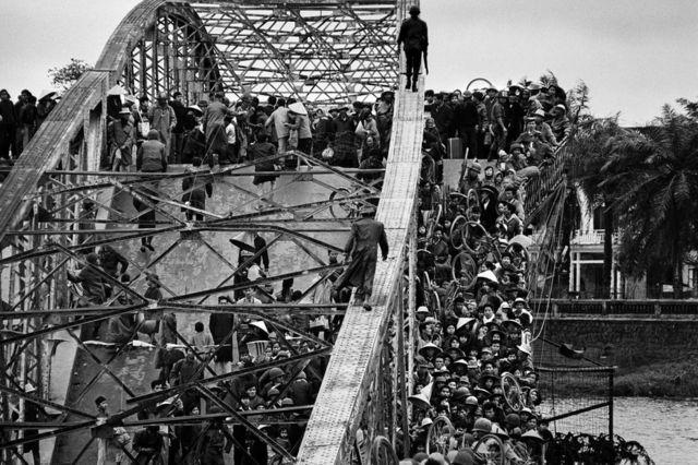 Thousands of civilians attempt to cross a bridge