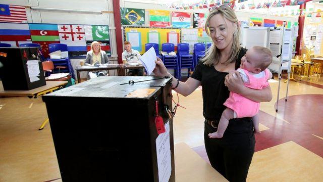 유권자가 아기와 함께 낙태 찬반 투표에 참여하고 있다