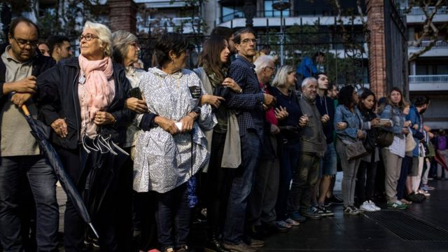 People join arms as they clear a path for the arrival of the official ballot boxes to arrive at the Escola Industrial of Barcelona school polling station on October 1, 2017 in Barcelona, Spain.