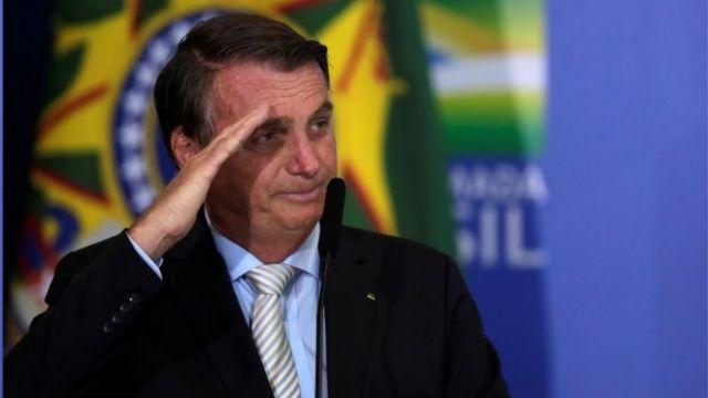Jair Bolsonaro faz continência diante da bandeira do Brasil