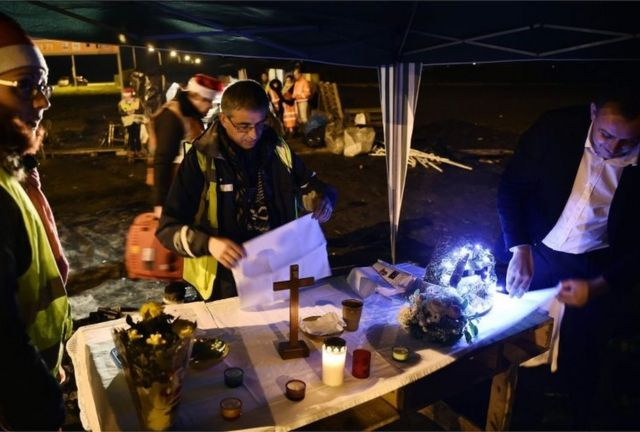 """A priest prepares for a Christmas Eve mass for """"yellow vests"""" protesters near a roundabout in Somain, northern France"""