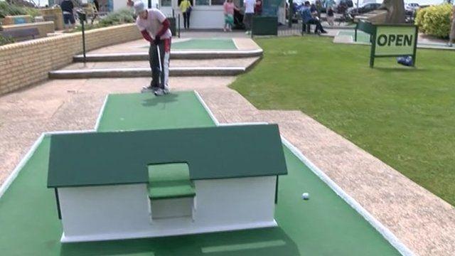 Golfer hitting a ball on the green