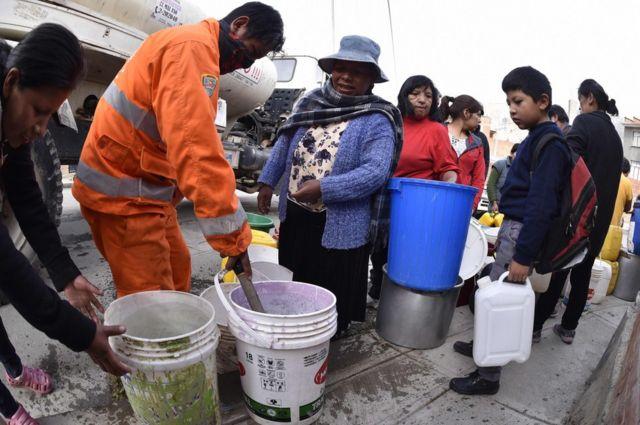 Vecinos reciben agua con cubos de camiones cisterna