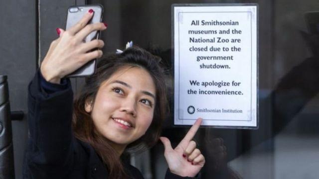 Du khách chụp ảnh trước biển báo đóng cửa của bảo tàng và Vườn thú Quốc gia ở Washington