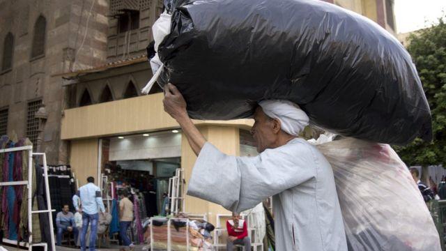 رجل مصري يحمل على رأسه كيسا بلاستيكيا